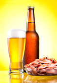 Brown bottle of beer with a condensate, a glass and a plate of b — Stock Photo