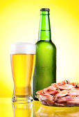 Green bottle of beer with a condensate, a glass and a plate of b — Stock Photo