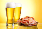 Two glass of beer and cooked shrimp on a plate on a yellow back — Stock Photo