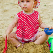 Beautiful little girl in red clothes, playing in a sandbox — Stock Photo