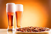 Two glass of beer and pizza over yellow background — Stock Photo
