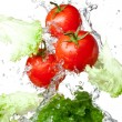 Three Fresh red Tomatoes and lettuce in splash water Isolated on — Stock Photo