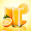 Two Glasses of Fresh Orange juice, half oranges and the leaves o — Stock Photo