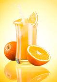 Splashing Fresh Orange Juice on yellow background — Stock Photo