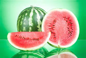Watermelon, half and Slice on a green background — Stockfoto