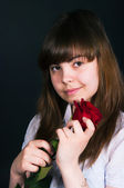 Girl with a rose on a black background — Stok fotoğraf