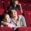 Loughing mother and daughter at the cinema — Stockfoto