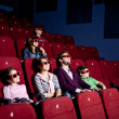 Parents with children watching a comedy — ストック写真