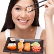 Smiling woman holding sushi roll with a chopsticks — Stock Photo #10959943