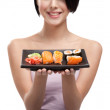 Young girl holding plate of sushi and smiling — Stock Photo