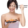 Smiling young female holding sushi with a chopsticks — Stock Photo #10959968