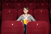 Young woman with popcorn in the movie theater — Stock Photo