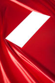 Envelope over red satin background — Stock Photo