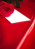 Envelope and red rose over silk background — Stock Photo