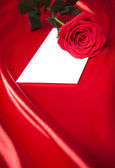 Envelope and red rose over silk or satin background — Stock Photo