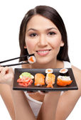Young attractive woman holding sushi with a chopsticks — Stock Photo