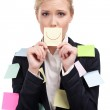 Attractive business woman holding a yellow sticker in front of her face — Stock Photo
