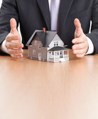 Businessman hands around house architectural model — Stock Photo