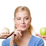 mladá žena je na výběr mezi dort a apple — Stock fotografie