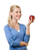 Smiling attractive woman holding red apple — Stock Photo