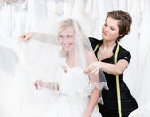 Shop assistant sets the veil of the bride — Stock Photo
