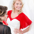 Stock Photo: Bride puts wedding gown to