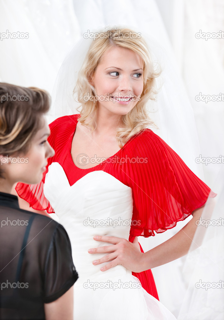 Bride puts the wedding gown to hesitating whether she should try it on or not — Stock Photo #11784764