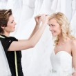 Shop assistant helps to fix the wedding tiara — Stock Photo
