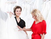 Two girls have a good look at the dress — Stock Photo