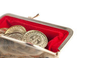 Scattered silver and gold coins are in hot red purse, isolated on white background — Stock Photo