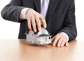 Businessman holding house architectural model — Stock Photo
