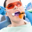 Dentist uses photopolymer lamp and dental mirror to treat teeth — Stock Photo