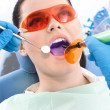Royalty-Free Stock Photo: Dentist uses photopolymer lamp and dental mirror to treat teeth
