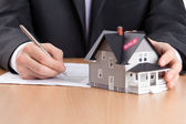 Businessman signs contract behind house architectural model — Stock Photo