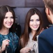 Two girls smiles at shop assistant — Stock Photo