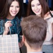 Two girls speak to salesperson — Stock Photo