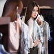 Стоковое фото: Trying on a dress and looking in the mirror