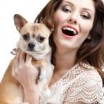 vacker kvinna håller på händerna en halm-färgad liten hund — Stockfoto