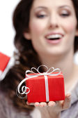 Young woman shows a gift — Stock Photo