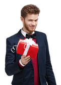Man in bow tie offers a present — Stock Photo