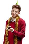 Homem sorridente com enfeites detém bolo pequeno — Fotografia Stock