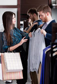 Consulting with girlfriend while choosing a stylish shirt — Foto Stock