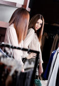 Admiring her beauty at the mirror in the store — Stock Photo