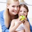 Smiley mum with her eating apple daughter — Stock Photo