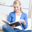 Beautiful woman reads the book lying on the sofa — Stock Photo #12287111
