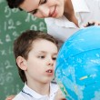 Little schoolboy uses terrestrial globe — Stock Photo