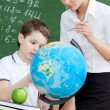 Stock Photo: Geography teacher explains something to the pupil