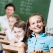 Smiley schoolgirl sits at the desk — Stock Photo #12287613
