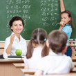 Teacher asks pupils at the chalkboard — Stock Photo