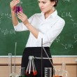 Smiley chemistry teacher examines conical flask — Stock Photo
